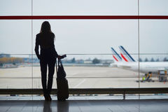 Young woman in the airport, looking through the window at planes Royalty Free Stock Photo