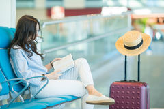 Young woman in an airport lounge reading book while waiting for flight aircraft. Airline passenger in an airport lounge waiting for flight aircraft Royalty Free Stock Photos