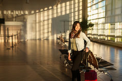 Young woman at airport terminal waiting room with trolley bag. Royalty Free Stock Images