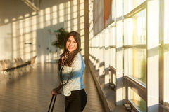 Young woman at airport terminal waiting room with trolley bag. Royalty Free Stock Photos