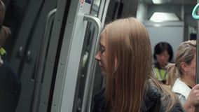 Young woman in an airport train connecting different terminals read her tickets.  stock video footage