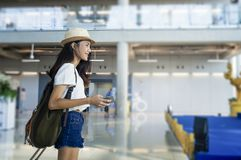 Young woman in airport waiting for air travel using smart phone. Travel Concept Stock Photography