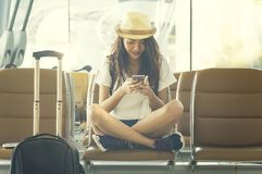 Young woman in airport waiting for air travel using smart phone. She is sitting with travel suitcase trolley, in waiting hall of departure lounge in airport Stock Photos