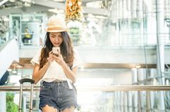 Young woman in airport waiting for air travel using smart phone. She is sitting with travel suitcase trolley, in waiting hall of departure lounge in airport Stock Photography