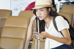 Young woman in airport waiting for air travel using smart phone. Travel Concept Stock Photos