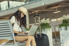 Young woman in airport waiting for air travel using tablet. She. Is sitting with travel suitcase trolley, in waiting hall of departure lounge in airport.Travel Royalty Free Stock Photography