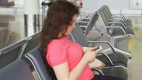 A young woman at the airport waiting for departure and looking at the smartphone. A woman at the airport waiting for departure and looking at the smartphone stock video footage