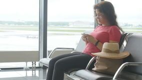 A young woman at the airport waiting for departure and looking at the smartphone. A woman at the airport waiting for departure and looking at the smartphone stock video