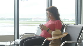 A young woman at the airport waiting for departure and looking at the smartphone. A woman at the airport waiting for departure and looking at the smartphone stock footage
