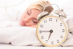 Young woman with alarm clock. Soon to wake up for sleeping attractive young woman with alarm clock royalty free stock photography