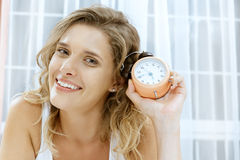Young woman with alarmclock on the bed. Stock Photo