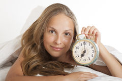 Young woman with alarmclock on the bed at morning Royalty Free Stock Photos
