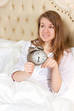 Young woman with alarmclock on the bed Royalty Free Stock Photography