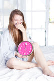 Young woman with alarmclock on the bed at morning Stock Photography