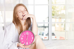 Young woman with alarmclock on the bed at morning Royalty Free Stock Image