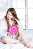 Young woman with alarmclock on the bed at morning Royalty Free Stock Images