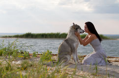 Young woman with alaskan malamute dog. Young adult woman with her favorite pet - alaskan malamute dog on the beach in the evening Stock Photo