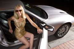 Young woman alighting from car at night, elevated view Royalty Free Stock Image