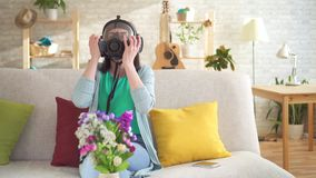 Young woman allergic sitting in a modern apartment, she sneezes and wears a respirator. Young woman sitting in a modern apartment allergic to flowers, she stock video