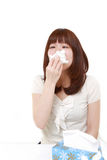 Young woman with an allergy sneezing into tissue Royalty Free Stock Photos