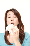 Young woman with an allergy sneezing into tissue Royalty Free Stock Photography