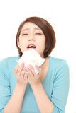 Young woman with an allergy sneezing into tissue Stock Images