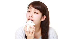 Young woman with an allergy sneezing into tissue Royalty Free Stock Image