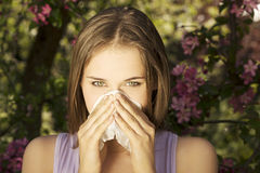 Young woman with allergy. During sunny day is wiping her nose Stock Images