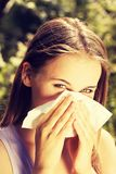 Young woman with allergy. During sunny day is wiping her nose Royalty Free Stock Photography