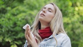 Young woman with with allergy symptom blowing nose standing in the park. Sick girl sneezing and blowing her nose into