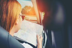Young woman alone car traveler with map on hatchback car Stock Photography