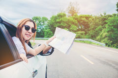 Young woman alone car traveler with map on hatchback car Royalty Free Stock Images
