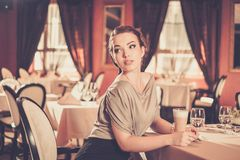 Young woman alone in a restaurant Royalty Free Stock Photo