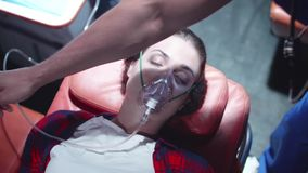 Young woman in ambulance, corpsman put on her face mask. Corpsman put an oxygen mask on woman`s face stock video