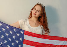 Young woman with american flag in hands looking at camera vintage colored image stock image