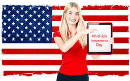 Young woman with american national flag. On the background holding tablet pc with sample text. 4th of July Independence Day celebration concept Stock Photography