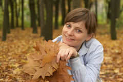 Young woman amongst yellow leaves. Outdoors smilling Stock Images