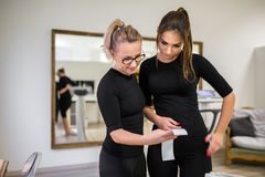 Young woman analyzing her results printout with personal trainer. Portrait of young women analyzing her results printout with personal trainer stock images