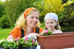 Young Woman And Little Girl Gardening In Spring, Planting Flower Seedlings, Smiling Mother And Her Happy Child Working In Garden Royalty Free Stock Images
