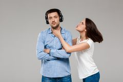Young woman angering with man in headphones over grey background. Royalty Free Stock Photos