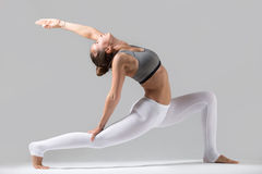 Young woman in anjaneyasana pose, grey studio background. Young attractive woman practicing fitness, standing in lunge exercise, yoga pose, working out wearing stock images
