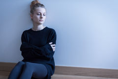 Young woman with anxiety disorder. Sitting on the floor stock photo