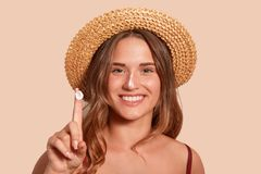 Young woman applaying sunblock on her face, and showinig her finger with sunscreen, model posing isolated over beige background, stock photos