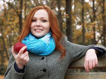Young woman with apple in autumn park, yellow leaves and trees stock photo