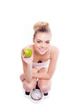 Young woman with an apple on a bathroom scale Stock Image