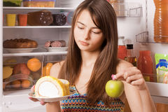 Young woman with apple and cake Royalty Free Stock Image