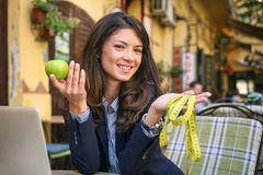 Young woman with apple and meter poses to camera. Young woman Stock Photography