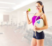 Young woman with apple and scales at gym club Stock Photography
