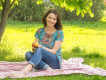 Young woman with an apple sitting on a green meadow in the park Stock Photography