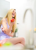 Young woman with apple sitting in kitchen Royalty Free Stock Image